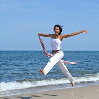 Zrelaksowana kobieta w podskoku nad brzegiem morza