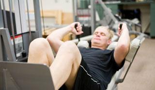 Mężczyzna ćwiczący na przyrządzie do ćwiczeń