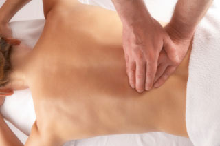 Kobieta leżąca na brzuchu podczas masażu leczniczego kręgosłupa