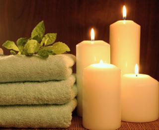 Ręczniki i zapalone świece wprowadzjące relaksujący klimat