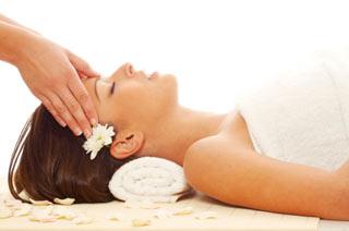 Kobieta leży podczas masażu głowy wśród płatków kwiatów