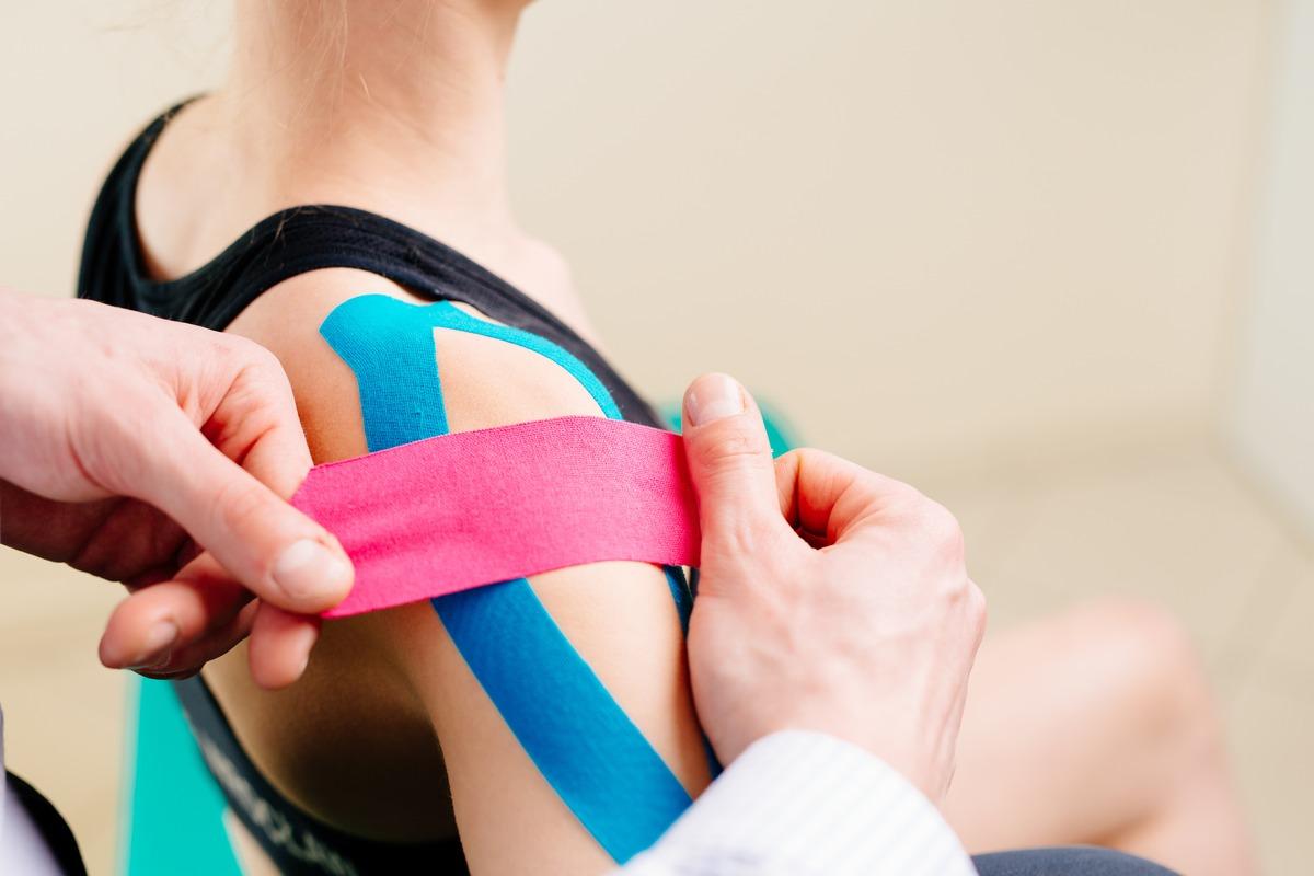 Fizjoterapeuta nakleja taśmy na ramieniu kobiety